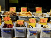 Chinese food items on sale displayed in sidewalk bins in afternoon sun in New York City´s Chinatown. Note labels in Chinese only.