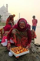 Families preparing offering in the Yamuna river behind the Taj Mahal.