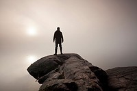 A man stands at the edge of a rocky outcrop looking into the fog as the sun rises. Algonquin Provincial Park, Ontario, Canada.