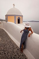 Woman in front of a yellow domed church in Fira town, Santorini, Cyclades Islands, Greek Islands, Greece, Europe.