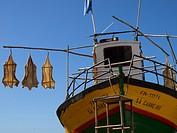 Dry cod fish and a colourful boat, Camera Do Lobos, Madeira island, Portugal.