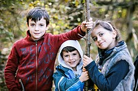 Portrait of three children in a forest in autumn
