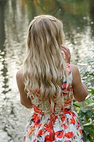 Young blond woman standing by the lake.