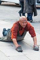 A pilgrim prostrating himself around the Barkhor circuit in Lhasa, Tibet.