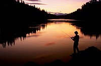 Angler fishing at sunset, Bulkley river, Smithers, BC, Canada.