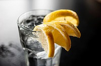A glass of water with lemon wedges on the edge of a glass on a table in a restaurant, Alabama.
