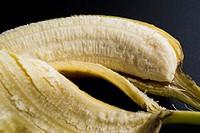 Macro shot of a partially peeled banana recling in its skin.