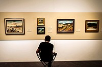 A sketch artist seated near paintings on the wall, Denver Art Gallery, Denver, USA
