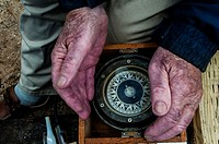 An old sailor cups his hands around an antique compass, Halifax, Nova Scotia, Canada