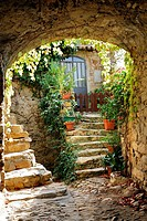 Stone framed entrance made of old bricks with door and plants, Bussana Vecchia, Liguria, Italy, Europe.