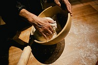 Hands kneading wheat bread dough on a wooden table.
