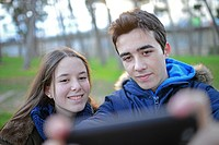 Teenagers taking a selfie in park.