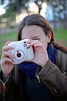 Cute teenager using an instant camera.