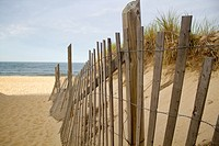 The Edge of a fence on a Sandy beach on the Cape cod shore in Cape Cod, Massachusset on a sunny day