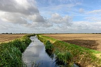 landscape of the marsh with a ditch between large fields, in distance wind turbines, under a bright sky, Romney Marsh, Kent.