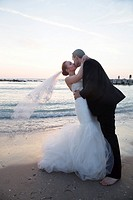 Bride and groom kissing on the beach on sunrise/ sunset background.