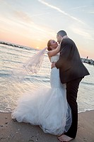 Bride and groom about to kiss on the beach on sunrise/ sunset background.