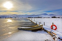 Small rowing boat used for fishing, sunk by the weight of snow, loch on Eaglesham Moor, near Glasgow, Scotland, UK. Image taken about 1 mile south of ...