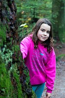 Young girl looking from behind a large tree in a temperate rain forest.