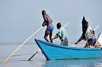 Fishers pushing their boat through the water at Lake Victoria, Kenya.