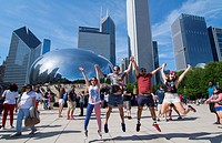 Chicago Illinois Millennium Park July 4th locals jumping for joy at Cloud Gate sculpture called The Bean with skyline in background skyscrapers in dow...