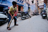 Boys playing cricket on the street.