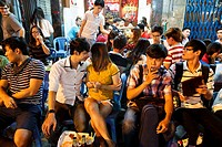 Young people sitting at a bar in Bui Vien Street in Pham Ngu Lao District, Ho Chi Minh City (Saigon), Vietnam.