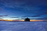 Twilight fades over a barn and snowy western Iowa landscape.