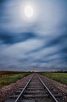 Fog blows west off the hills in western Iowa above train tracks lit by the moon which also had a vivid corona.