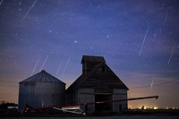 Geminid meteors streak across the sky behind a barn in western Iowa.