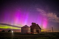 Nothern lights dance above the Iowa landscape.