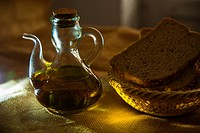Still life: oil bottle and bread in a basket. Close view.