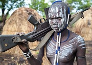 Woman belonging to the Mursi tribe. Omo valley ( Ethiopia). She is holding a Kalashnikov.