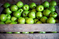 Wooden box with organic green apples in a market