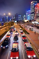 cars wait at traffic lights with Hong Kong skyline in the background.