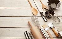 Kitchen baking utensils against white desk.