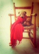 Two teddy bears sitting on child's rocking chair.