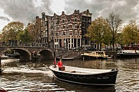 A boat passes the Hemonybrug bridge at Keizersgracht and Leidsegracht in the Singel Canel in Amsterdam.