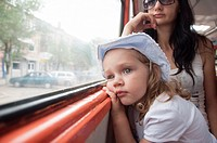 Little girl and mom goes to tram. Girl tired, thoughtfully, looking out the window.