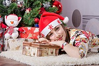 The girl lying on the carpet around the Christmas tree. In her hands a big box with a present. The girl looks frame.