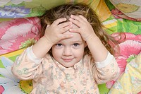 Two-year-old girl is in bed. The girl hugged his head in his hands and fun looking at the picture. Photo above. Portrait.