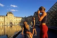 young tourist people, Louvre Pyramid by Ming Pei, in the main courtyard Cour Napoleon of Palais du Louvre, 1st arrondissement, Paris, Ile de France re...