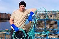 Martin McAskill, prawn fisherman, standing with his prawn nets at Port Glasgow harbour, near Glasgow, Scotland, UK.