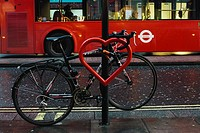 Red heart and a bike tied to a street lamp. Oxford street, London.