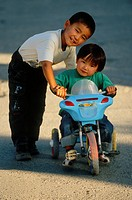 Boy and girl playing with toy motorbike, Kochkor, Kyrgyzstan.