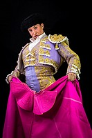 Woman bullfighter holding capote pink on black background.