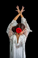 Flamenco dancer backs with white dress and hands crossed up on his back on black background.