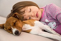 Toddler girl sleeping next to mixed breed puppy dog.