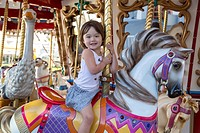 Happy girl riding the merry go round.