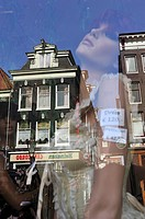 A mannequin in a shop window with reflection of a building. Amsterdam, The Netherlands.